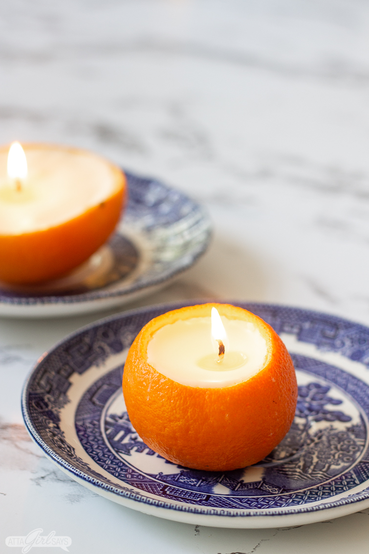mandarin orange candle on a blue china plate with a navel orange scented candle in the background on a marble countertop
