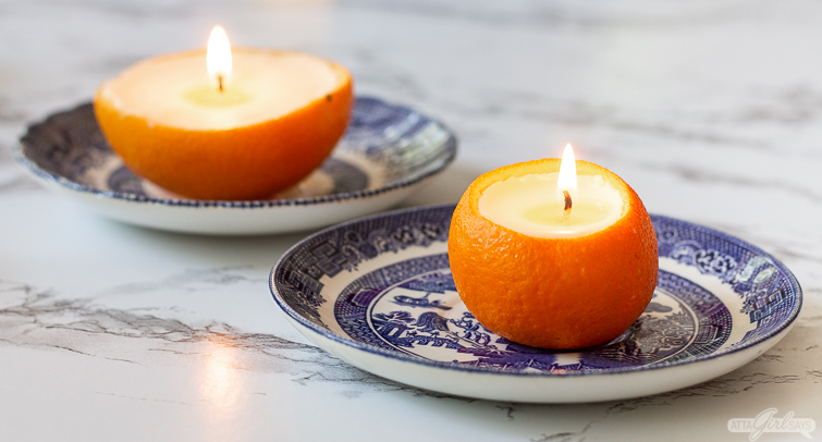 two orange peel candles on blue and white china plates