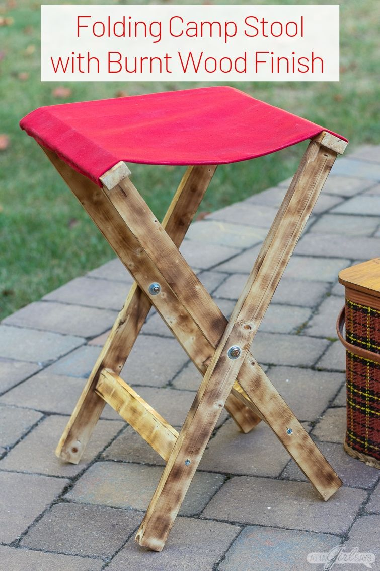 folding wood camp stool with a waxed canvas seat and a burned wood finish
