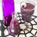 overhead shot of a glass flask and skull goblet filled with purple Halloween punch sitting beside a purple bottle