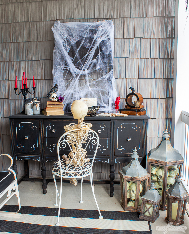 skeleton sitting in front of a black desk on a Halloween front porch
