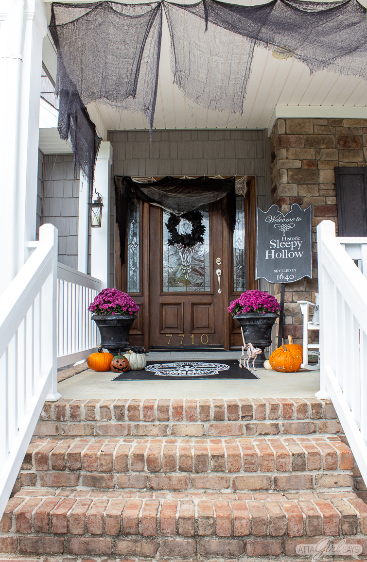 Spooky Halloween front porch with creepy cloth, pumpkins and a Sleepy Hollow sign