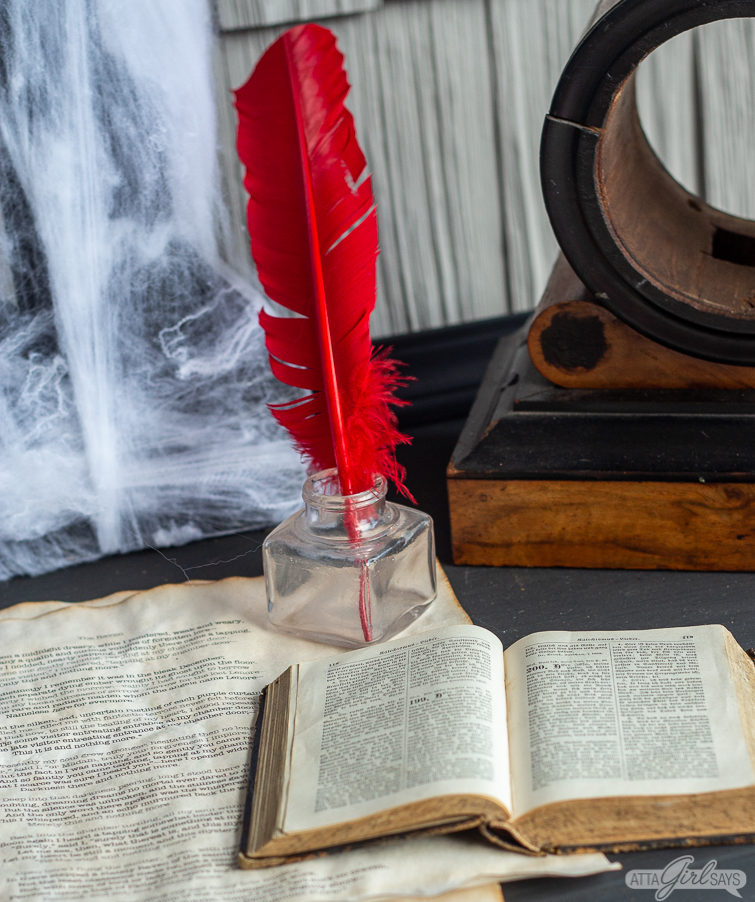 red feather quill in a glass jar on top of old parchment and beside an old book