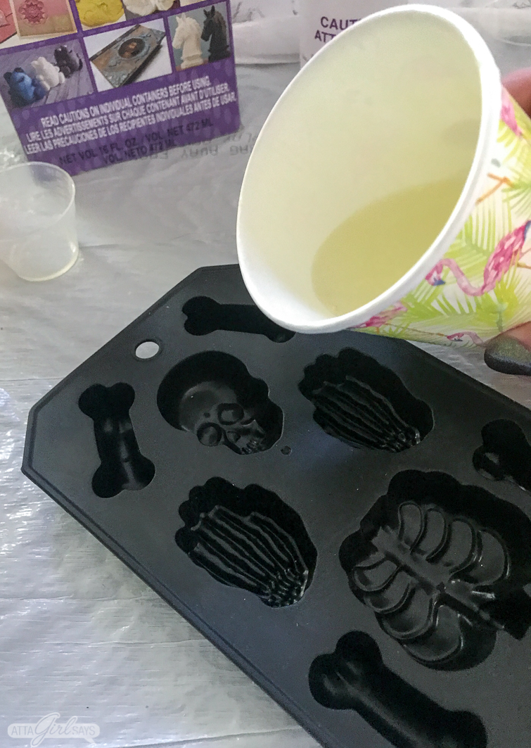 pouring liquid resin into a silicone ice cube tray