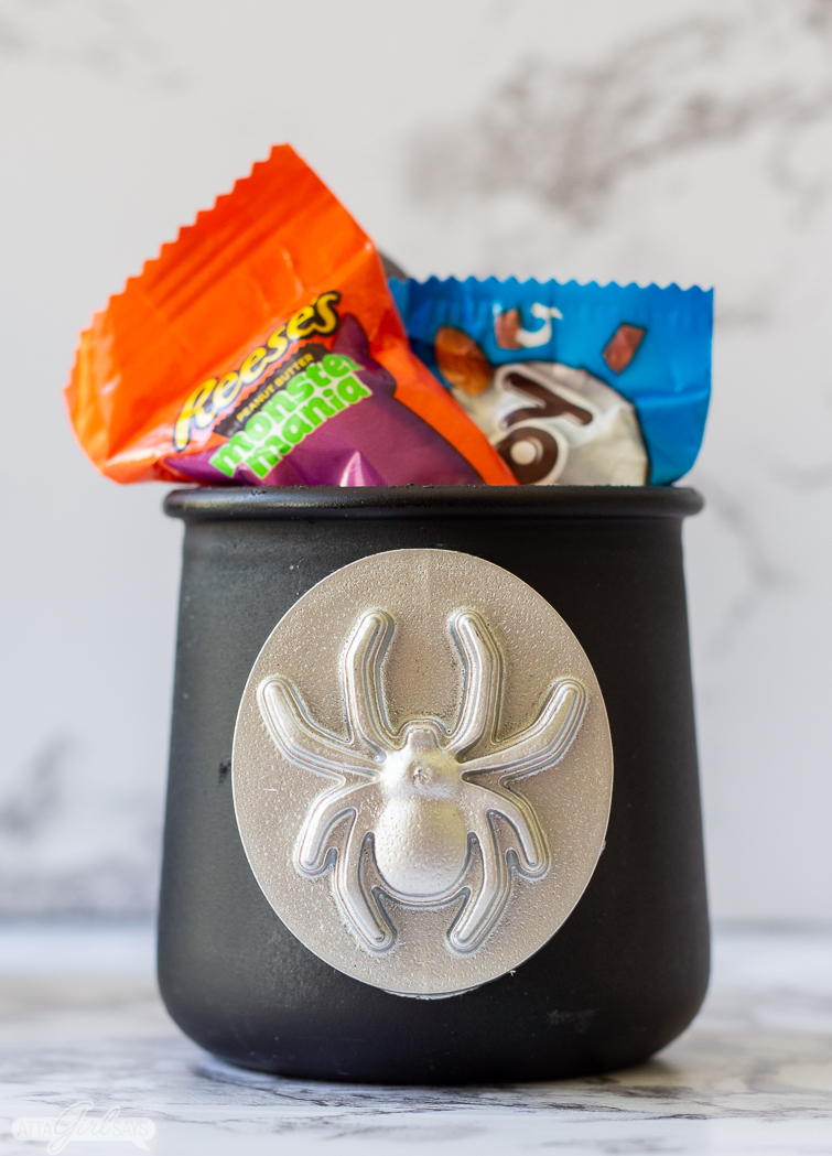 black yogurt jar with a spider medallion filled with Halloween candy