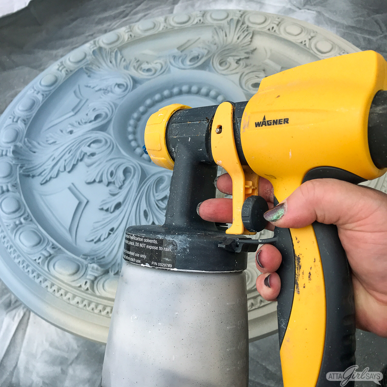 Wagner FLEXiO paint sprayer beside a painted decorative ceiling medallion