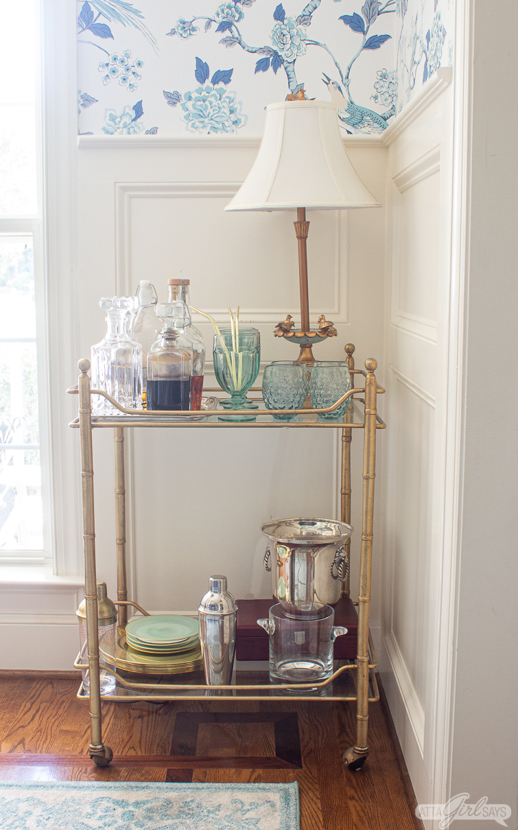 faux bamboo bar cart with green and blue glassware and crystal