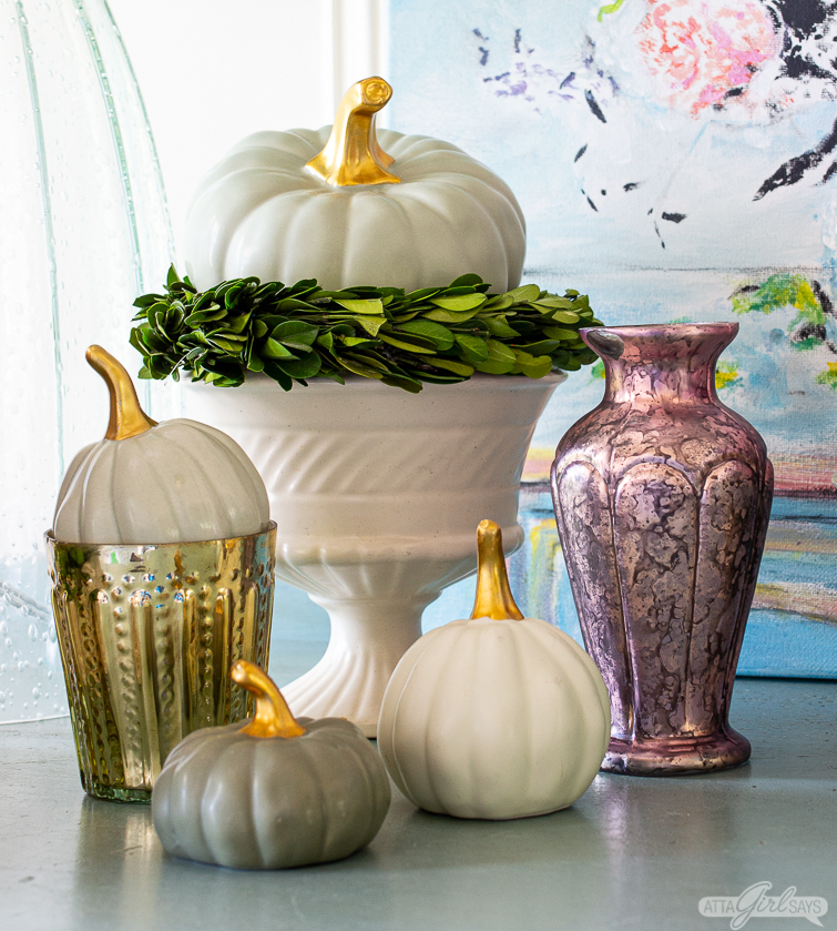 ceramic pumpkins, vintage pottery and mercury glass votives and vases on a painted buffet