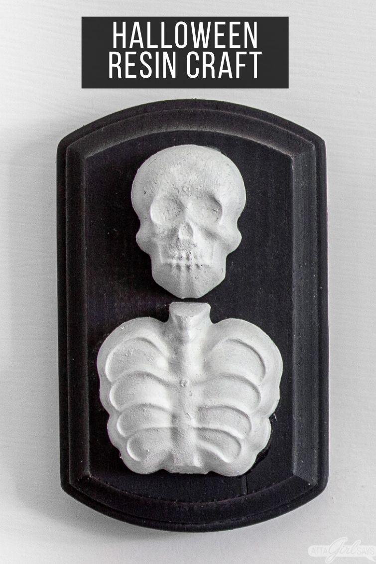 resin skeleton on a black wooden plaque