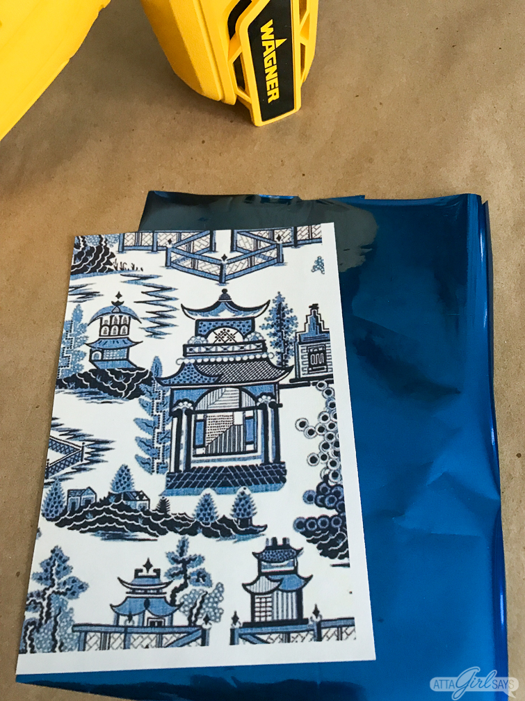 chinoiserie patterned paper sitting on a sheet of blue metallic foil