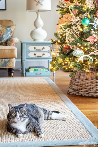 tabby cat laying on a seagrass rug in front of a Christmas tree