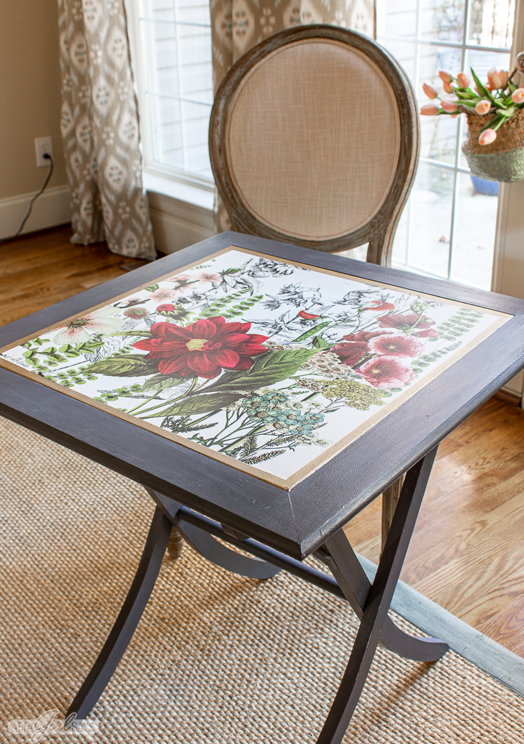 square folding table with a floral inset top beside a Louis chair