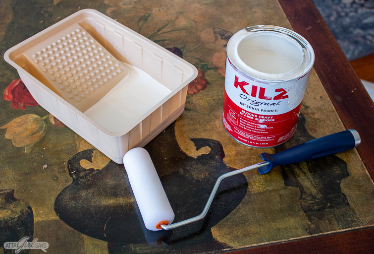 roller and can of KILZ primer on a floral tabletop