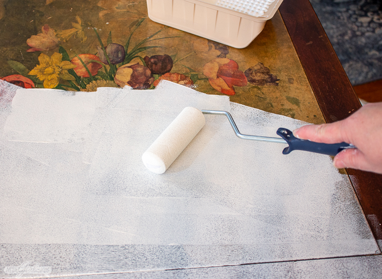 using a roller to apply KILZ primer to a wooden tabletop