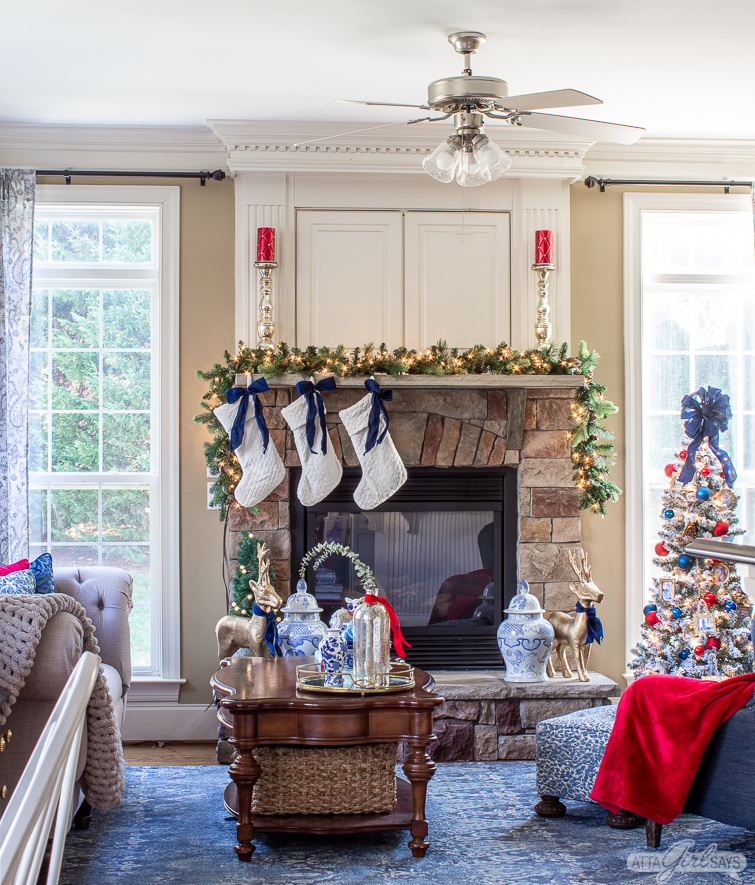 stone fireplace mantel with a TV cabinet above it decorated for Christmas