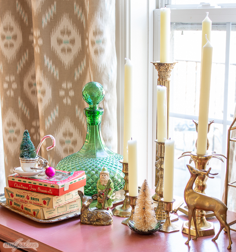 pink table with brass candlesticks, vintage Christmas ornaments and brass reindeer figures