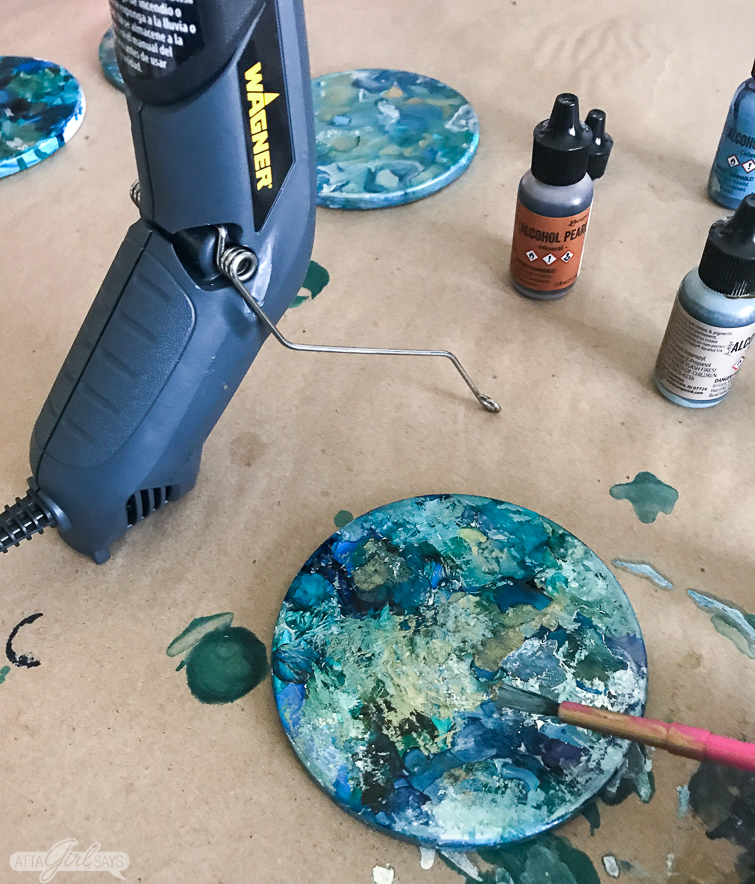 using a paintbrush to add an impressionistic look to alcohol ink coasters
