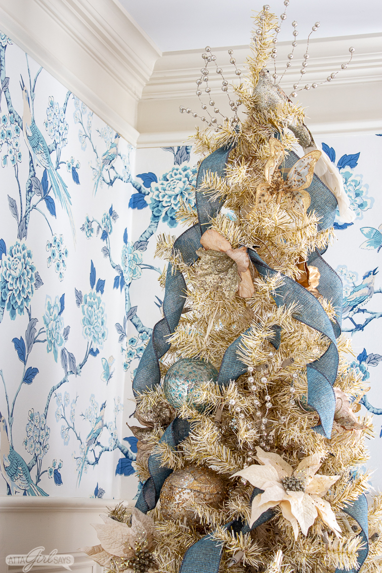 gold Christmas tree decorated with blue ribbon, gold flowers and birds in a formal dining room with toile wallpaper