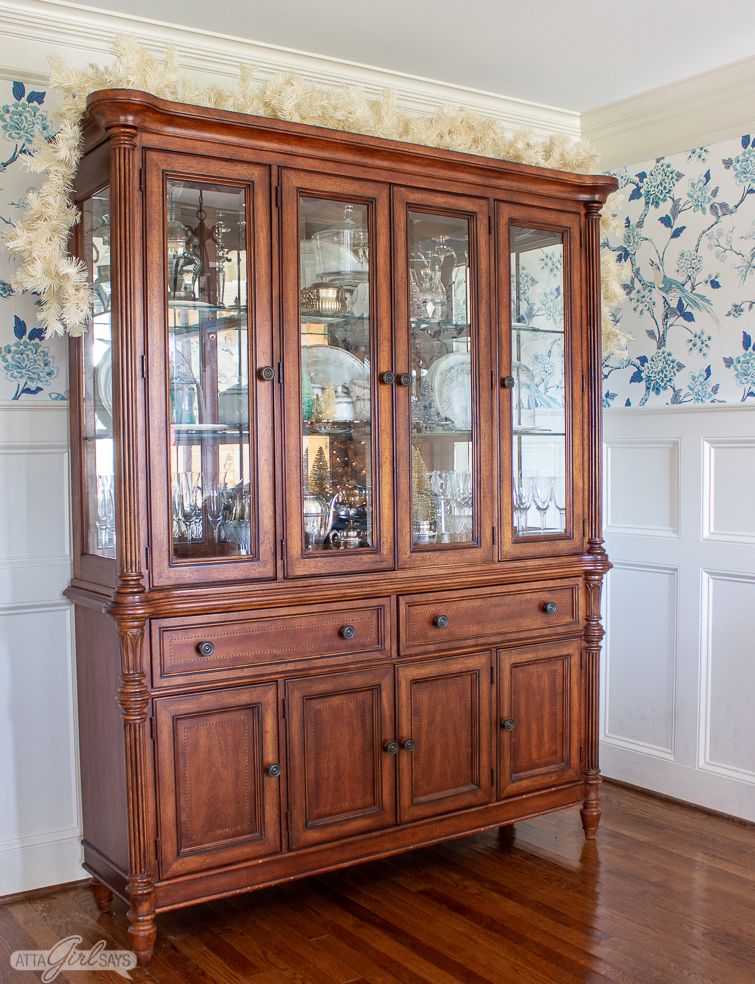 china cabinet with a garland on top of it for Christmas