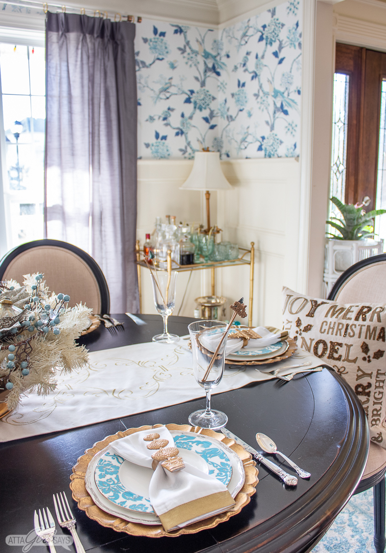 aqua blue and white plates on a holiday table with a gold bamboo bar cart in the background