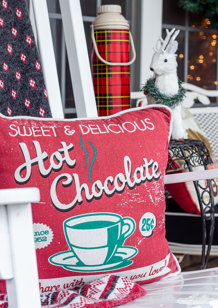 hot chocolate pillow used as front porch Christmas decorations on a white rocking chair