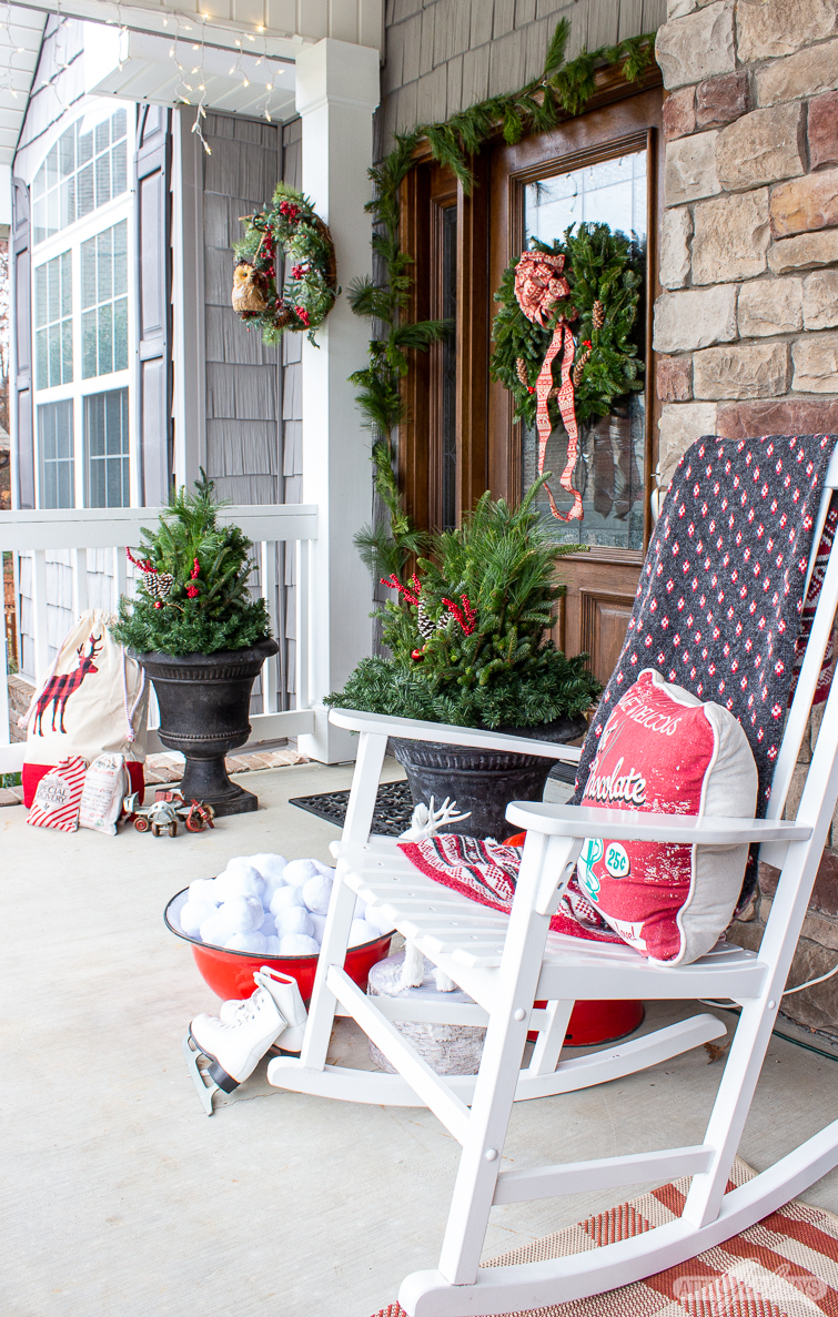 rocking chair with Christmas blanket and pillows with two evergreen-filled urns in the background on a porch