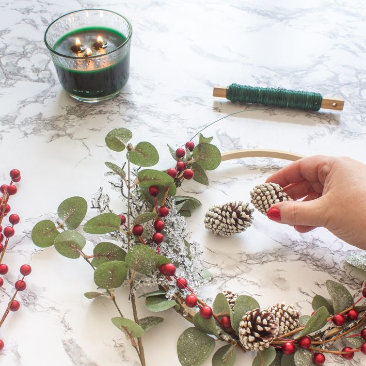 adding miniature pinecones to a Christmas embroidery hoop wreath with eucalyptus