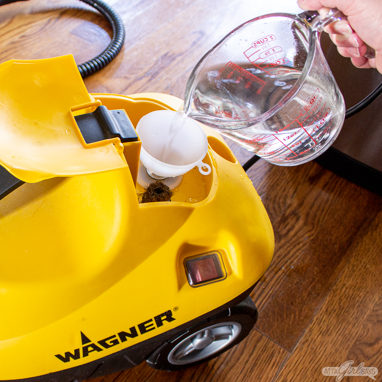 using a funnel and measuring cup to fill a steam cleaner