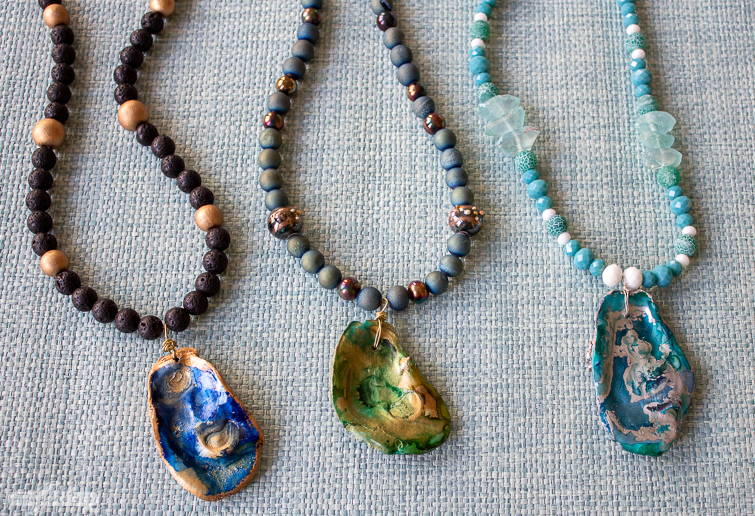 three alcohol ink oyster shell pendant necklaces on grasscloth